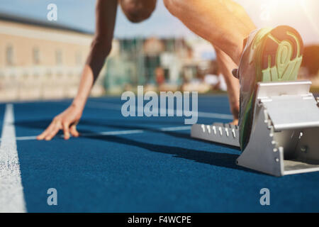 Feet on starting block ready for a spring start.  Focus on leg of a athlete about to start a race in stadium with - Stock Photo