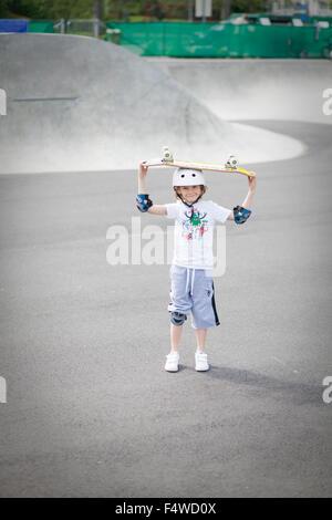 Sweden, Vastergotland, Lerum, Portrait of boy (8-9) with skateboard standing in skatepark - Stock Photo