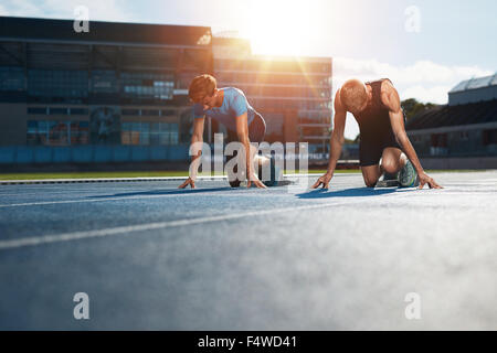 Young athletes preparing to race in start blocks in stadium. Sprinters at starting blocks ready for race with sun - Stock Photo