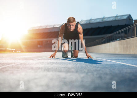 Young man athlete in starting position ready to start a race. Male sprinter ready for a run on racetrack looking - Stock Photo