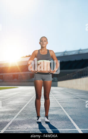 Full length shot of professional female athlete standing with her hands on hips looking confidently at camera. Runner - Stock Photo