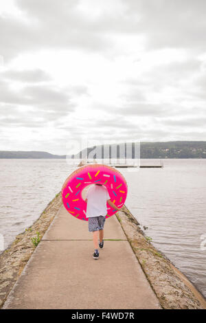 Sweden, Vastergotland, Lerum, rear view of boy (10-11) with inflatable ring on pier - Stock Photo