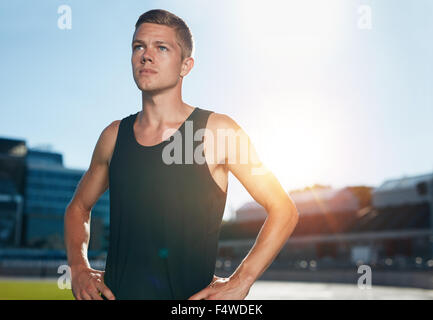 Young male runner standing with his hands on hips looking away. Determined athlete on race track in athletics stadium - Stock Photo