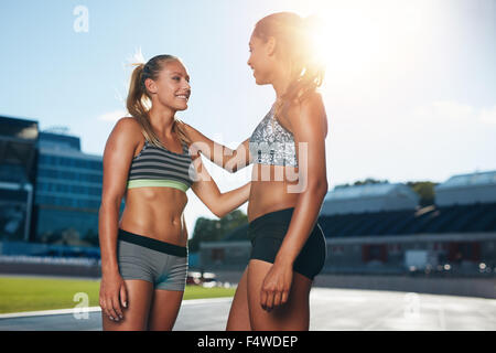 Two young female runner talking with each other after a run at stadium race track on a bright sunlight. Professional - Stock Photo