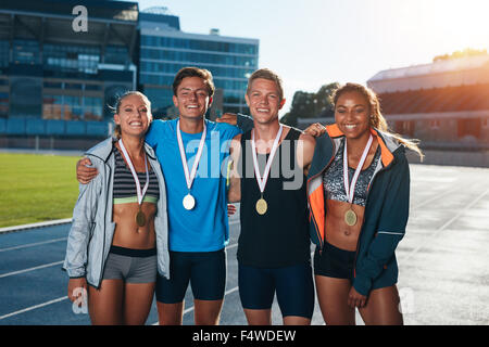 Group of athletes with medals .Two young woman and man together looking at camera and smiling while standing on - Stock Photo