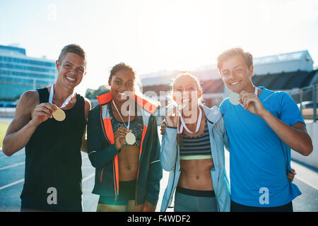 Portrait of ecstatic young runners showing medals. Young men and women looking excited after winner a running race. - Stock Photo