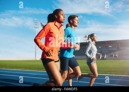 Group of runners running on race track in stadium. Young male and female athletes practicing together on racetrack. - Stock Photo
