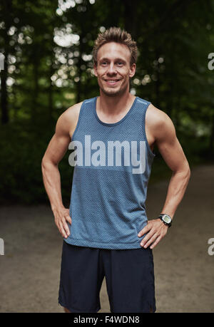 Smiling fit young man enjoying a healthy lifestyle standing outdoors in a park in his sportswear with his hands - Stock Photo