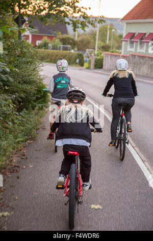 Mother and children (10-11, 12-13) cycling on street - Stock Photo