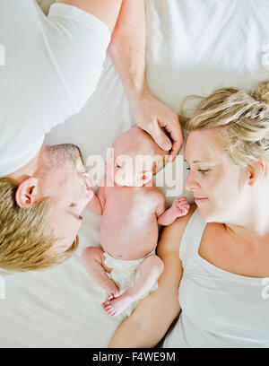 Baby boy (0-1 months) with his parents on bed