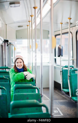 Young woman sitting in tram - Stock Photo