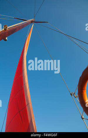 Yacht mast and rigging on a blue sky background during sailing in the sea. - Stock Photo