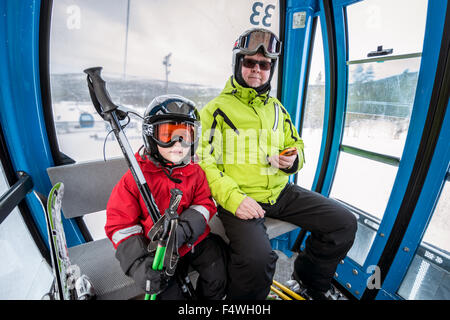 Finland, Lapland, Levi, Grandfather and grandson (6-7) in ski lift - Stock Photo