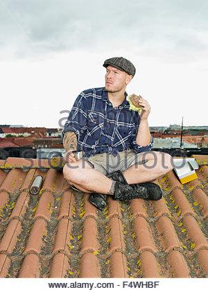 Finland, Uusimaa, Helsinki, Toolo, Man taking a break on roof - Stock Photo