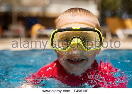 Turkey, Mugla, Marmaris, Portrait of boy (6-7) in swimming pool with swimming goggles - Stock Photo