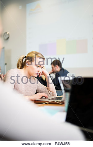 Woman using laptop in office - Stock Photo
