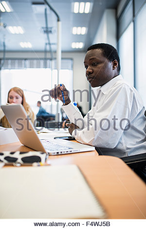 Man sitting at desk in office - Stock Photo