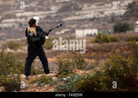 Ramallah, West Bank, Palestinian Territory. 23rd Oct, 2015. A female Israeli border police fires tear gas towards - Stock Photo