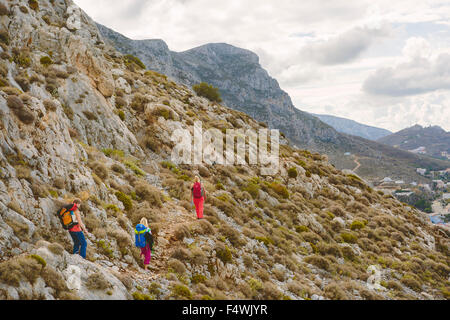 Greece, Dodecanese, Kalymnos, Hikers on mountainside - Stock Photo