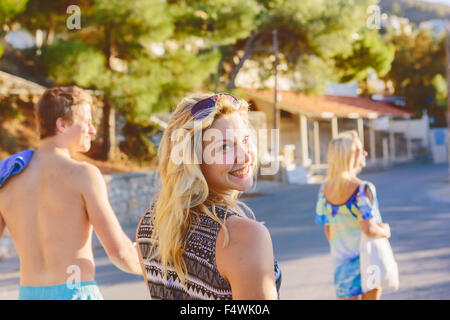 Greece, Dodecanese, Kalymnos, Smiling woman on town street looking over shoulder - Stock Photo