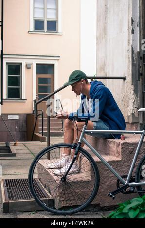 Finland, Pohjanmaa, Pietarsaari, Man sitting on porch and using mobile phone - Stock Photo