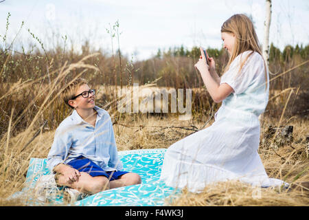 Finland, Keski-Suomi, Aanekoski, Girl (12-13) making picture of boy (12-13) sitting on blanket in meadow - Stock Photo