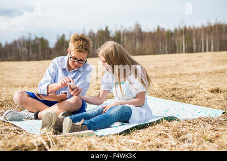 Finland, Keski-Suomi, Aanekoski, Girl (12-13) and boy (12-13) sitting on blanket in field and looking on mobile - Stock Photo
