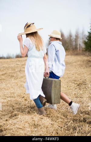 Finland, Keski-Suomi, Aanekoski, Girl (12-13) and boy (12-13) walking in field and carrying suitcase - Stock Photo