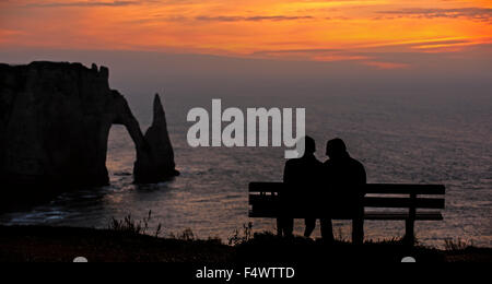 Tourists sitting on bench looking at Porte D'Aval, natural arch in chalk cliffs at Etretat at sunset, Upper Normandy, - Stock Photo