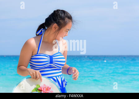 Tourist girl in a blue white striped swimsuit standing with happiness on the beautiful beach and sea during summer - Stock Photo