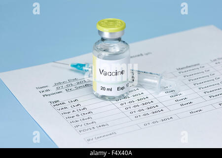 Vaccine vial with immunization record and syringe on white background. Label and record are fictitious. - Stock Photo
