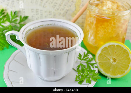 Hot tea with parsley, lemon and honey in a jar - Stock Photo