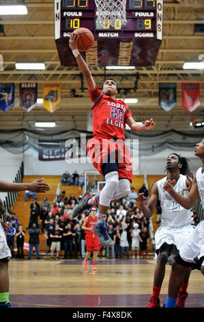Player elevates well off the floor to lay in two points as the defense can only watch during a high school basketball - Stock Photo