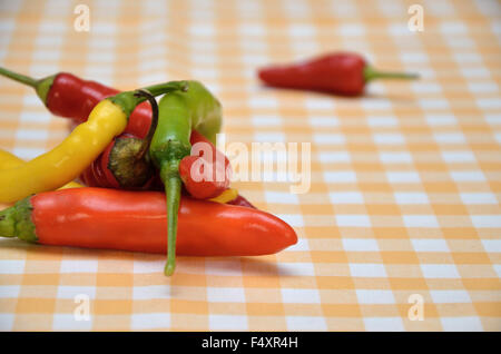 Pile of red, orange, green and yellow hot chili peppers on white-yellow tablecloth with a red pepper in background - Stock Photo