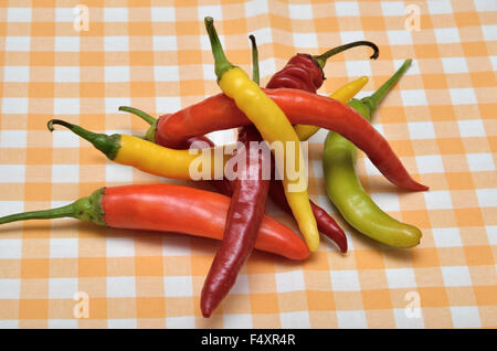 Pile of red, orange, green and yellow hot chili peppers on white-yellow tablecloth - Stock Photo