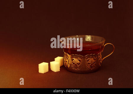 Cup of tea with cubes of sugar in dark room - Stock Photo