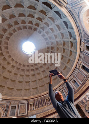 A tourist is taking a photo of the interior of the ancient Roman Pantheon temple. - Stock Photo