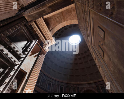 Sunlight is shining into the ancient Roman Pantheon temple through the characteristic hole in the middle of its - Stock Photo