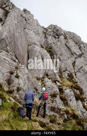 Two rock climbers preparing to climb Grooved Arete HVD 4a on Mount Tryfan east face in Snowdonia National Park. - Stock Photo