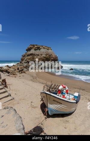 Fishing boat drawn up on the beach at Porto Novo Portugal - Stock Photo