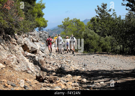 Seniors walking group and guide walking along a rocky rural road near Kyrenia in Turkish North Cyprus  KATHY DEWITT - Stock Photo