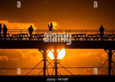 Aberystwyth Wales UK, Saturday 24 October 2015 UK Weather - People are silhouetted against the fiery sunset as they - Stock Photo