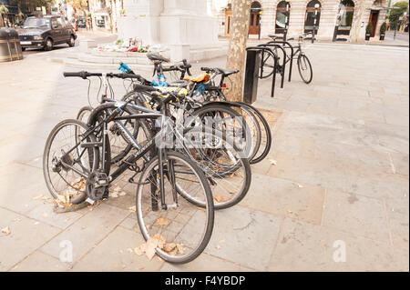 Massive numbers of bikes chained up on trees racks in center of flagstone pavement Trafalgar Square Postoffice - Stock Photo