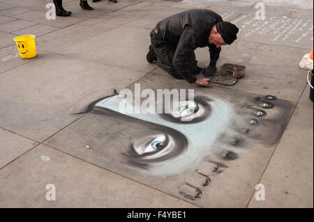 street artist drawing and sketching up on the Trafalgar pavement flagstones in chalk sketches of face and eyes marking - Stock Photo