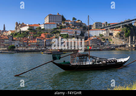 The Rabelo boat  used to transport Port Wine from the Douro Valley down river to near Porto against backdrop of - Stock Photo
