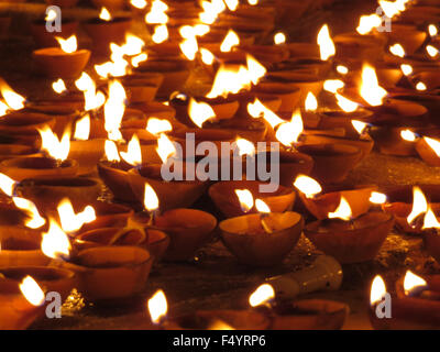 Traditional oil lamps in earthen pot lit up on the festive occasion of Diwali in India. - Stock Photo
