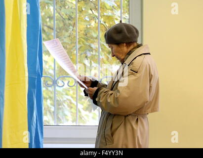 Kiev, Ukraine. 25th Oct, 2015. A woman reading a ballot at a polling station during local elections. © Maxim Pab/TASS/Alamy - Stock Photo