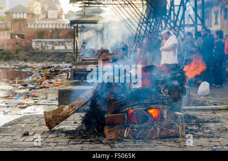 Burning ghats with ongoing cremations near Pashupatinath Temple - Stock Photo