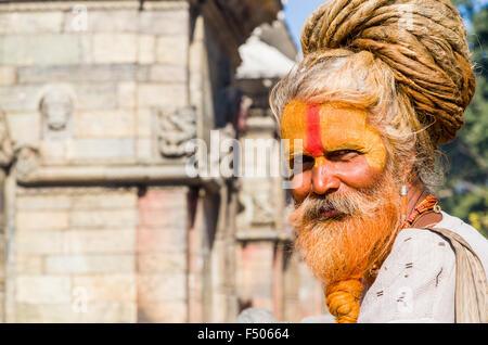 Portrait of a Sadhu, Holy Man, sitting opposite the burning ghats near Pashupatinath Temple - Stock Photo