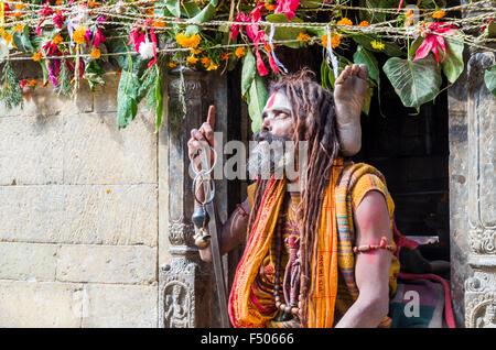 Sadhu, Holy Man, practicing yoga opposite the burning ghats near Pashupatinath Temple - Stock Photo